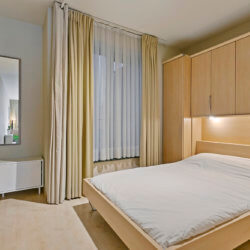 double bed with storage in studio apartment