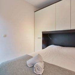 living room of serviced studio apartment with double bed and storage