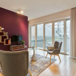 living room of serviced studio apartment with cable television and natural light