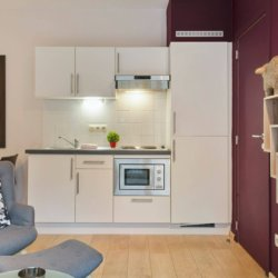 living room of serviced studio apartment with fully equipped kitchen