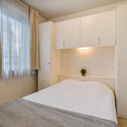 double bed with wardrobe storage and view onto church in sablon brussels