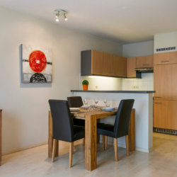 dining table and fully equipped kithcen with artwork on wall in serviced apartment