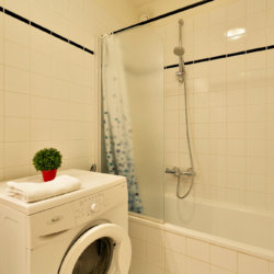 washing machine and bathroom with bathtub in bbf apartment in etterbeek