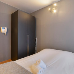 double bed with storage wardrobe towels and linen