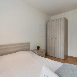 spacious double bed with storage wardrobe next to EU