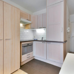 fully equipped kitchen with cupboard storage in furnished studio apartment in european quarter