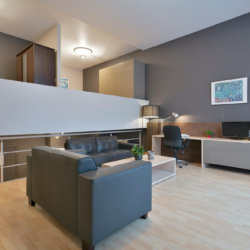 spacious living room with sofa and cable television in serviced apartment