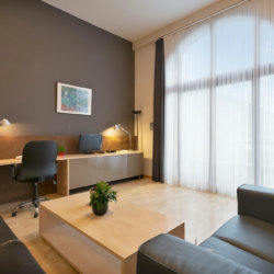 high ceilings in living space with office desk to work from home
