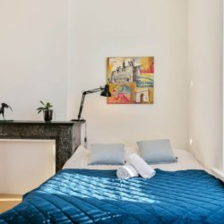 double bed in spacious bedroom with fireplace in brussels city