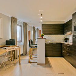 fully equipped kitchen with high bench and bar stools in serviced studio apartment