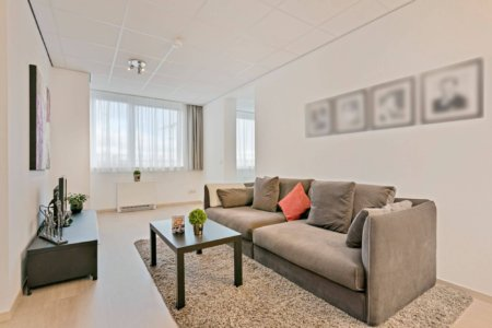 spacious sofa with artwork tv and table in two bedroom serviced apartment