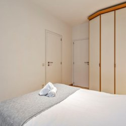 double bed in master bedroom with built in wardrobes near bois de la cambre